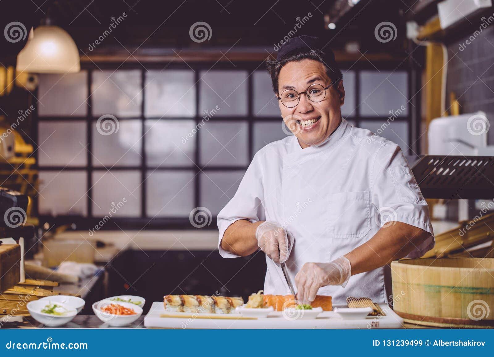Внушительный усмехаясь китайский человек используя нож для того чтобы отрезать суши в части