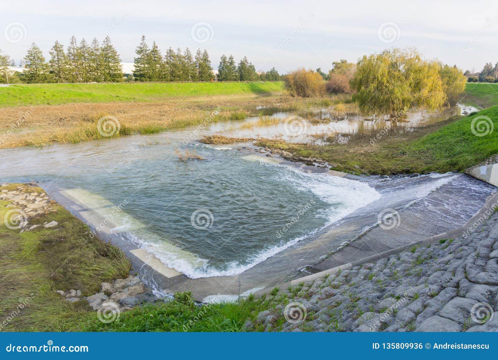 Вода будучи выпусканным в Реке Guadalupe на станции шторма Глен прохода, Santa Clara, юге San Francisco Bay, Калифорния