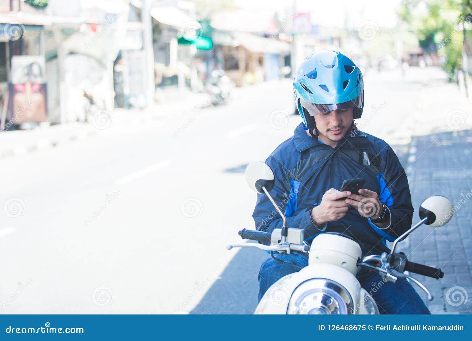 Водитель такси мотоцикла отправляя СМС на мобильном телефоне на стороне