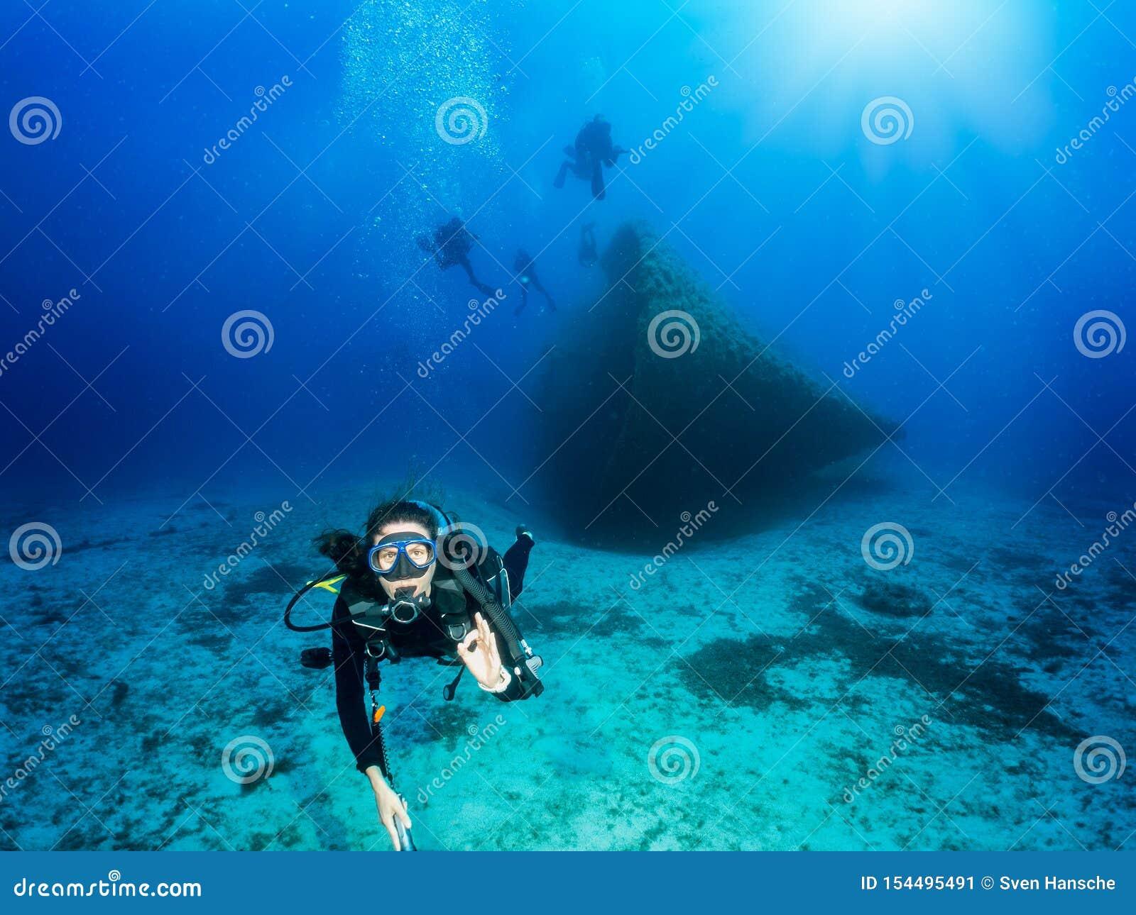 Водолаз акваланга показывает что ОК подписывает в сини, Эгейском море в Греции