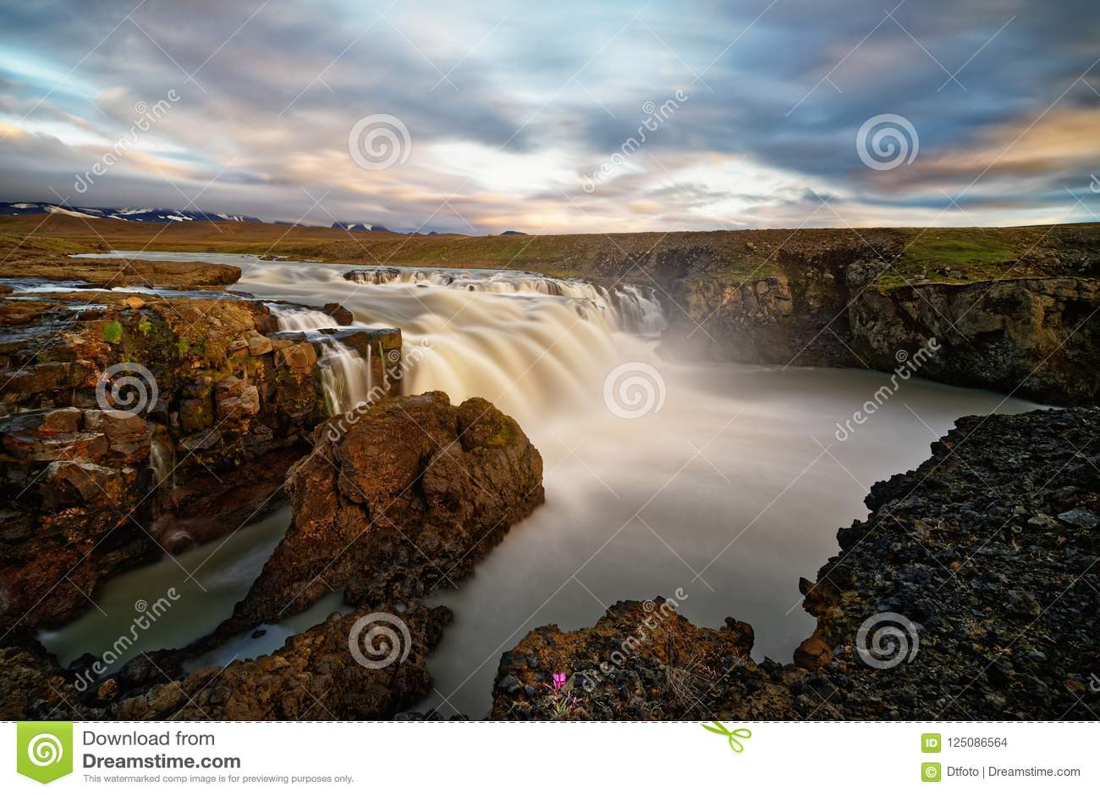 Водопад в одичалом ландшафте в свете вечера