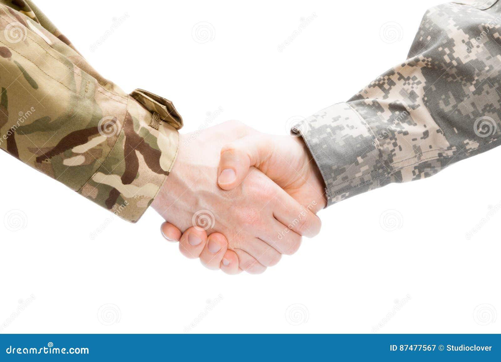 2 военного тряся руки на белой предпосылке - близкой поднимающей вверх съемке студии