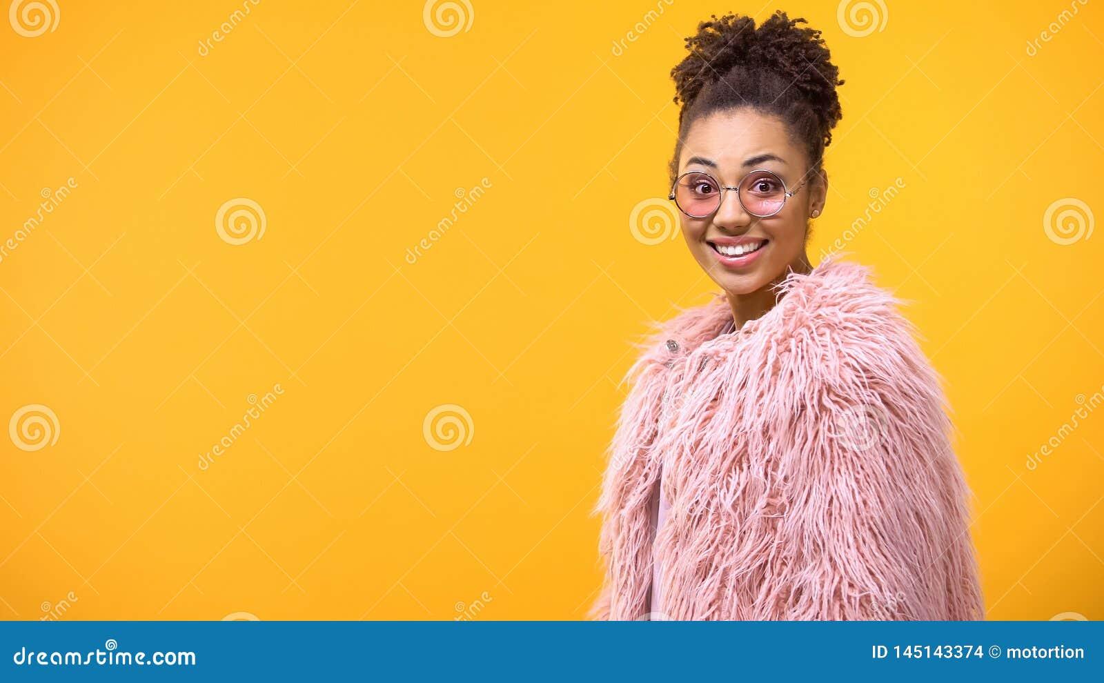 Возбужденная молодая женщина в розовых eyeglasses смотря камеру, изумление