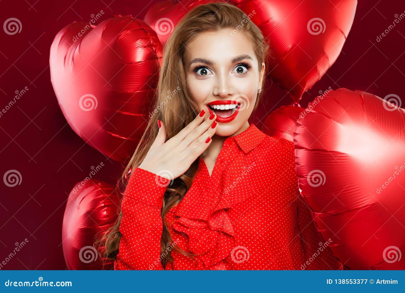 Возбужденная молодая женщина с красными воздушными шарами сердца Удивленная девушка с красным макияжем губ, длинное вьющиеся воло