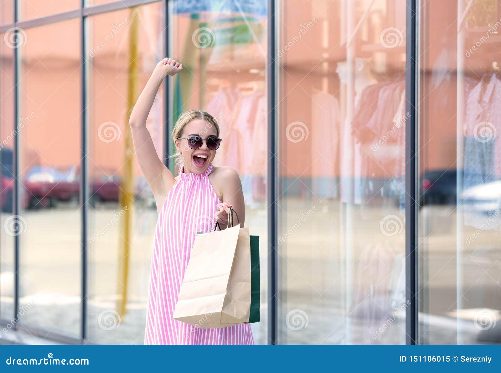 Возбужденная молодая женщина с хозяйственными сумками на улице города