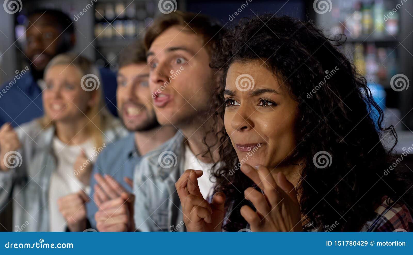 Возбужденные друзья пересекая пальцы смотря конкуренцию ТВ, вентиляторы на спортивном мероприятии