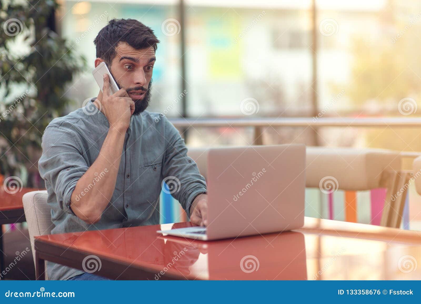 Возбужденный счастливый бородатый фрилансер читая электронную почту с результатами о победе в современном онлайн состязании сидя