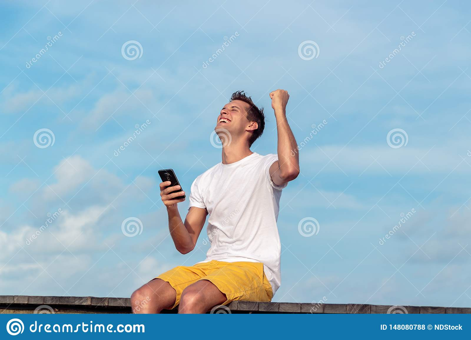 Возбужденный человек держа смартфон и выигрывая на линии на тропическом назначении