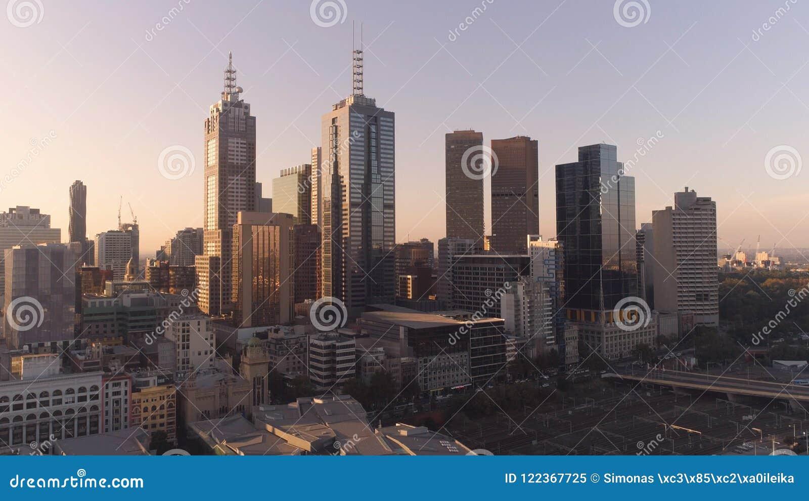Воздушная съемка небоскребов Мельбурна городских в заходе солнца Мельбурн, Виктория, Австралия