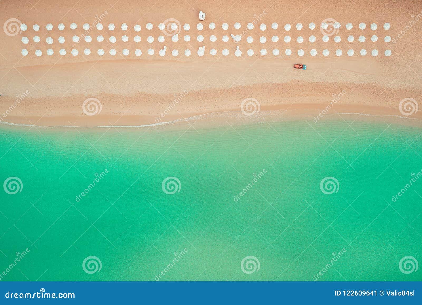 Воздушное взгляд сверху на пляже Зонтики, песок и волны моря