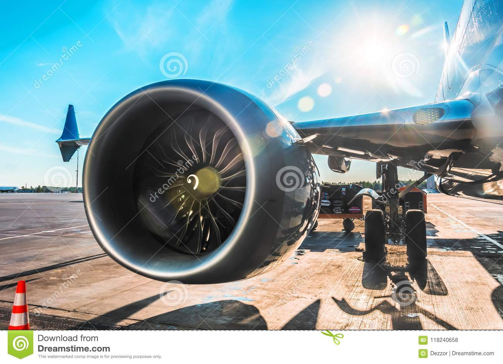 Воздушное судно припарковано на авиапорте перед отклонением, взгляде на крыле двигателя шестерни шкафа шасси, на солнечный день с