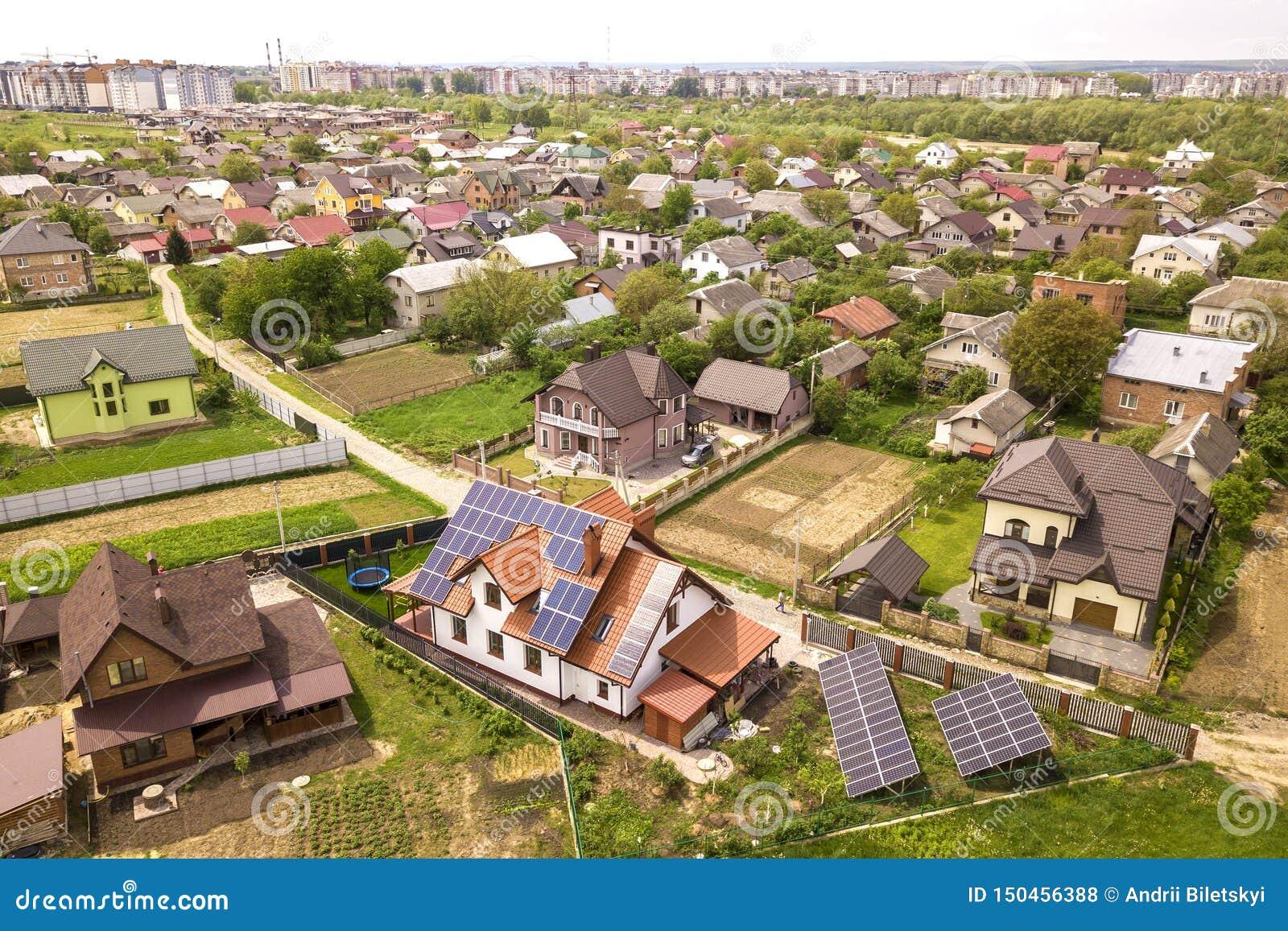 Воздушный взгляд сверху нового современного жилого коттеджа дома с системой панелей голубого сияющего солнечного фото voltaic на