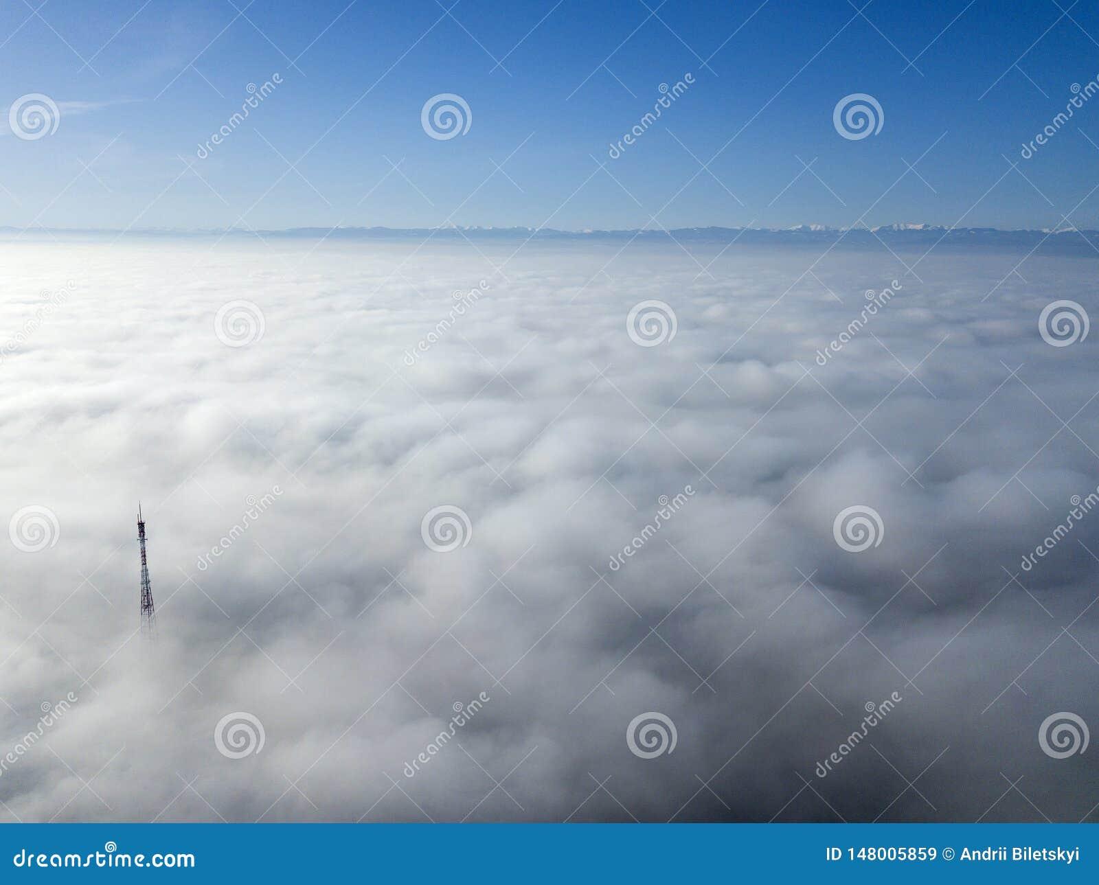 Воздушный взгляд сверху туманного пасмурного ландшафта с верхней частью радио или антенны ТВ на предпосылке космоса экземпляра го