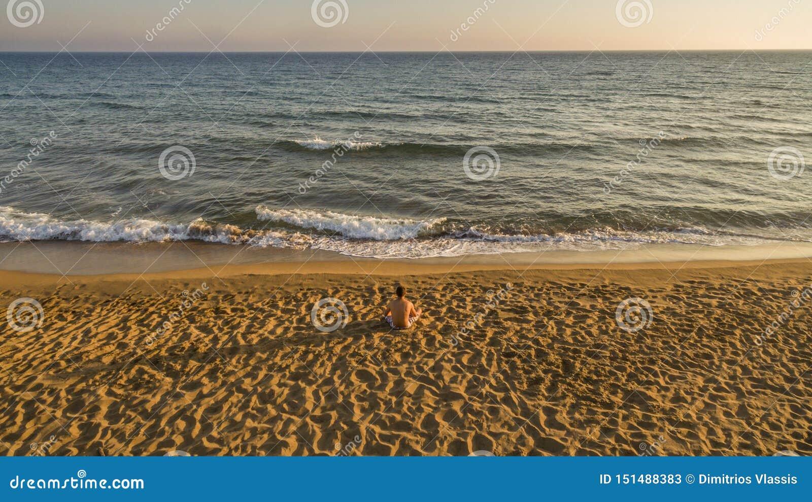 Воздушный взгляд трутня уединенного человека ослабляя на тихом пляже только перед заходом солнца