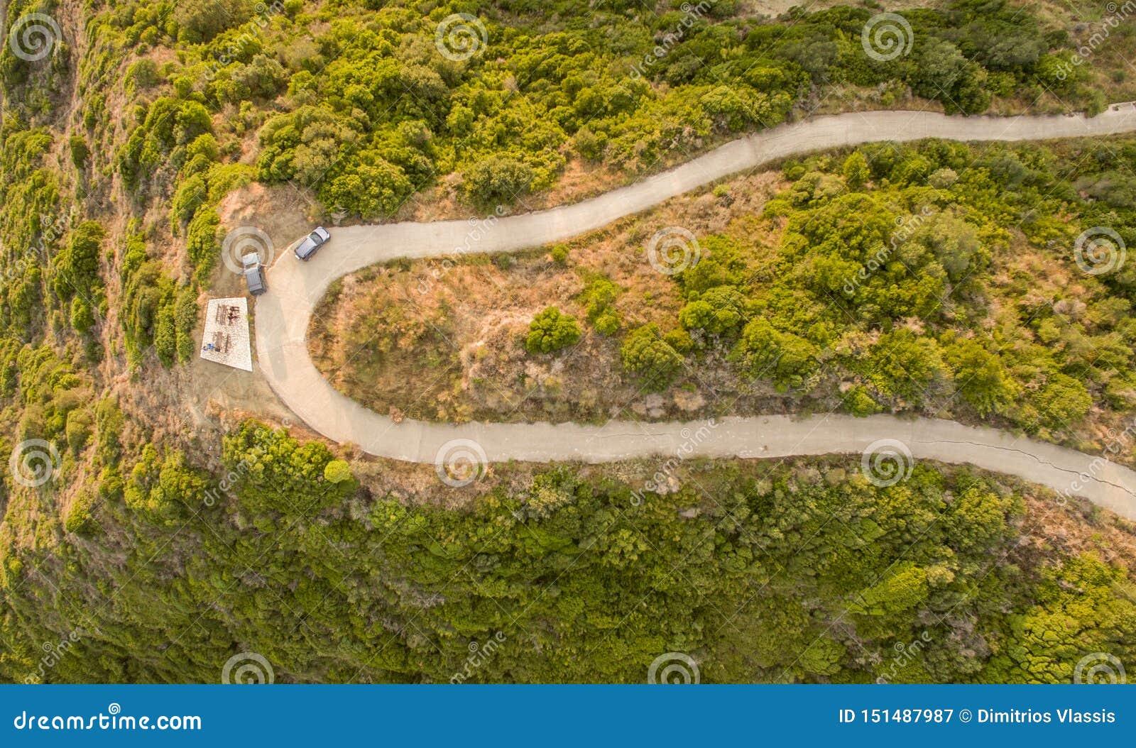Воздушный взгляд трутня twisty дороги на сельской местности в Корфу Греции