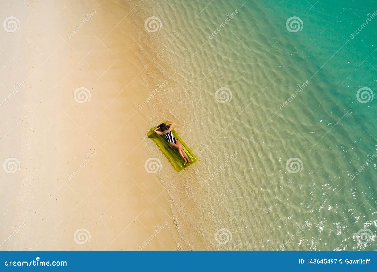 Воздушный вид с воздуха трутня красивой девушки имея потеху на солнечном тропическом пляже Сейшельские островы