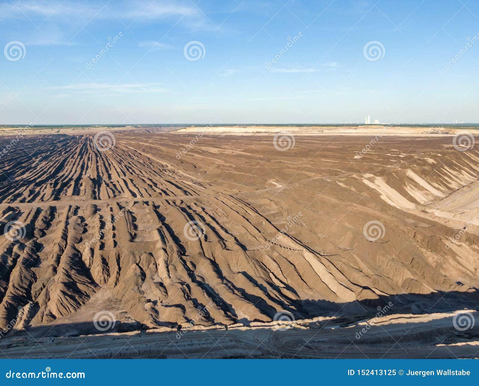 Воздушный выравниваясь взгляд захода солнца Welzow Süd, одного из самое большое рабочее немецкое открытого - брошенные шахты лигн