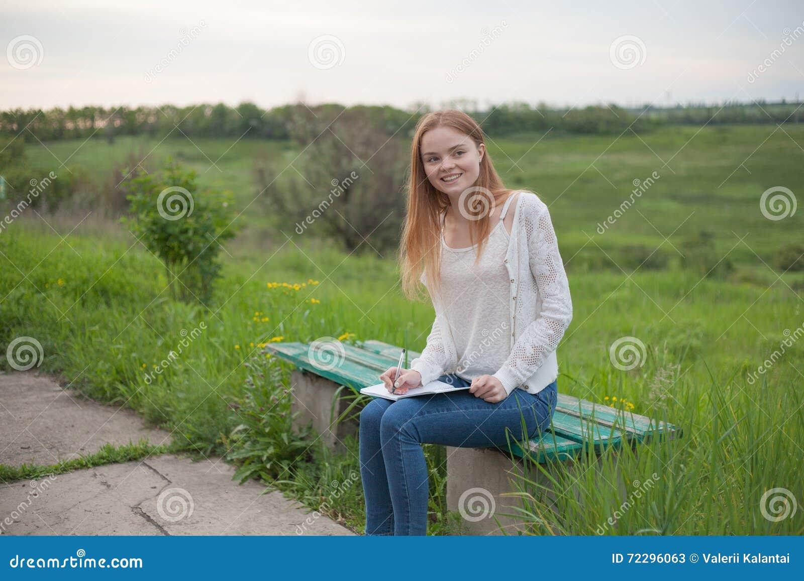 Download Возникновение счастливой девушки европейское сидя на стенде с тетрадью и ручкой Стоковое Изображение - изображение насчитывающей природа, примечание: 72296063