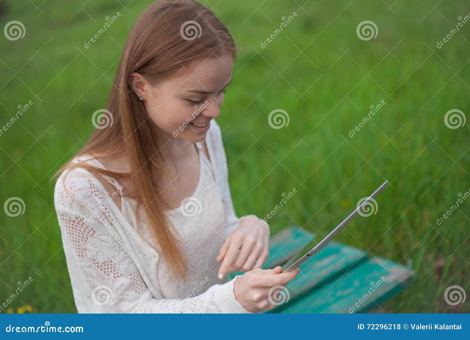 Download Возникновение счастливой девушки европейское сидя на стенде с компьтер-книжкой Стоковое Фото - изображение насчитывающей green, лето: 72296218
