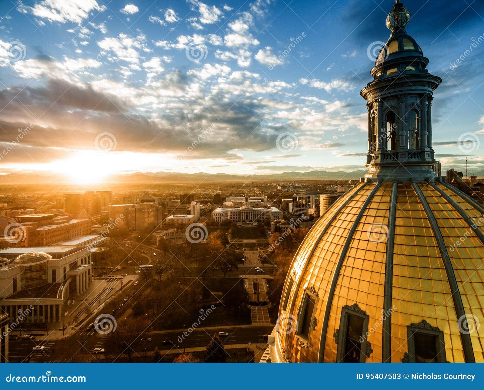Воздушный фотоснимок трутня - сногсшибательный золотой заход солнца над зданием столицы государства Колорадо & скалистыми горами,