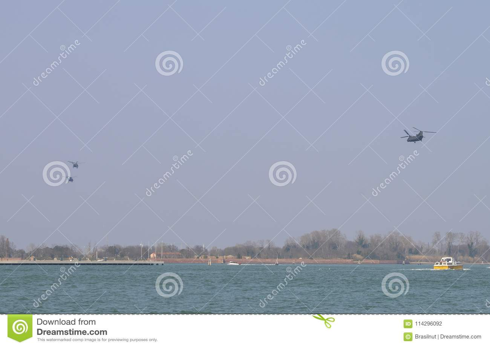 Воинские вертолеты в образовании над венецианской рубрикой лагуны к аэробазе Aviano в северовосточной Италии