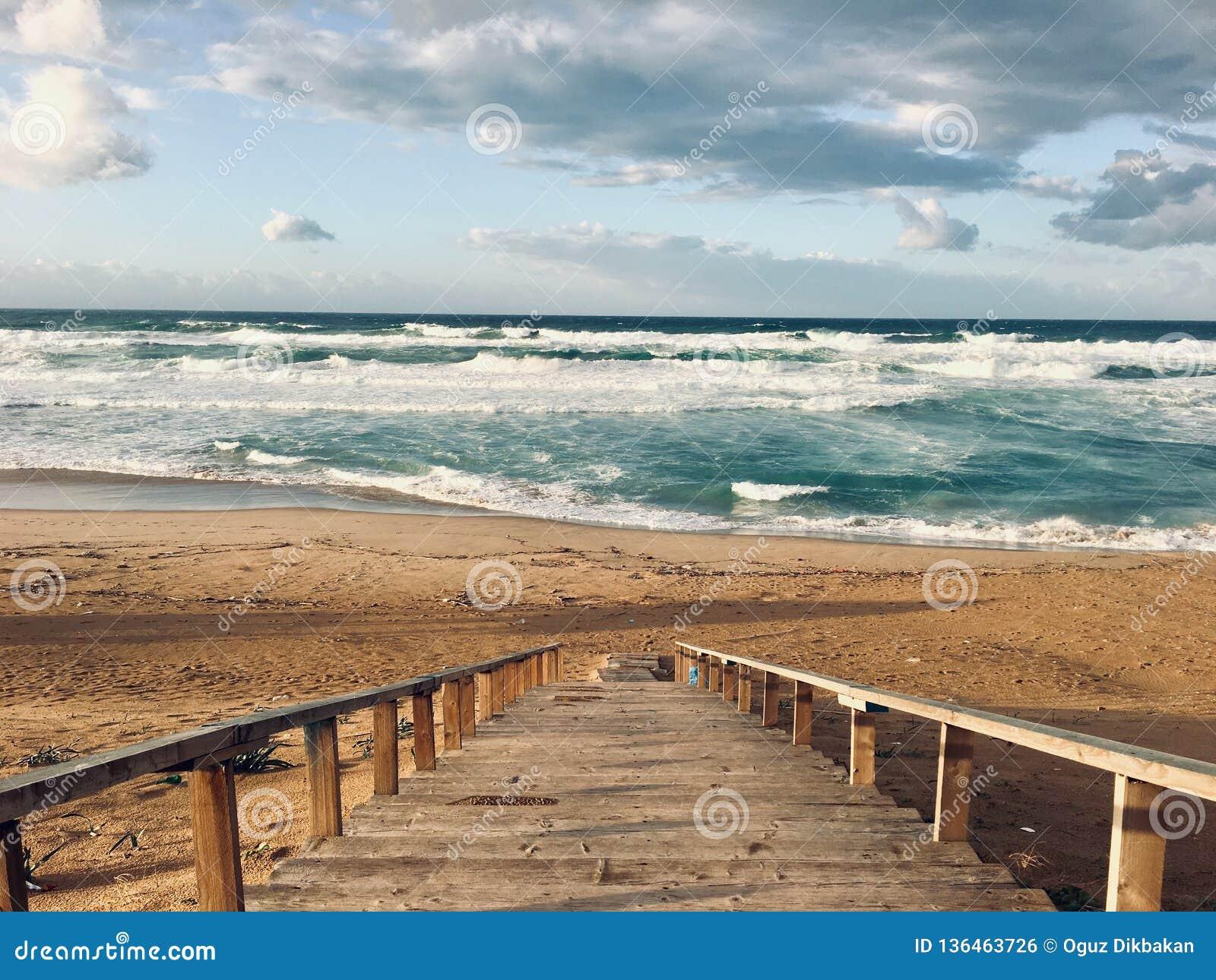 Волнистое Средиземное море с лестницами на времени захода солнца в Skikda Алжире