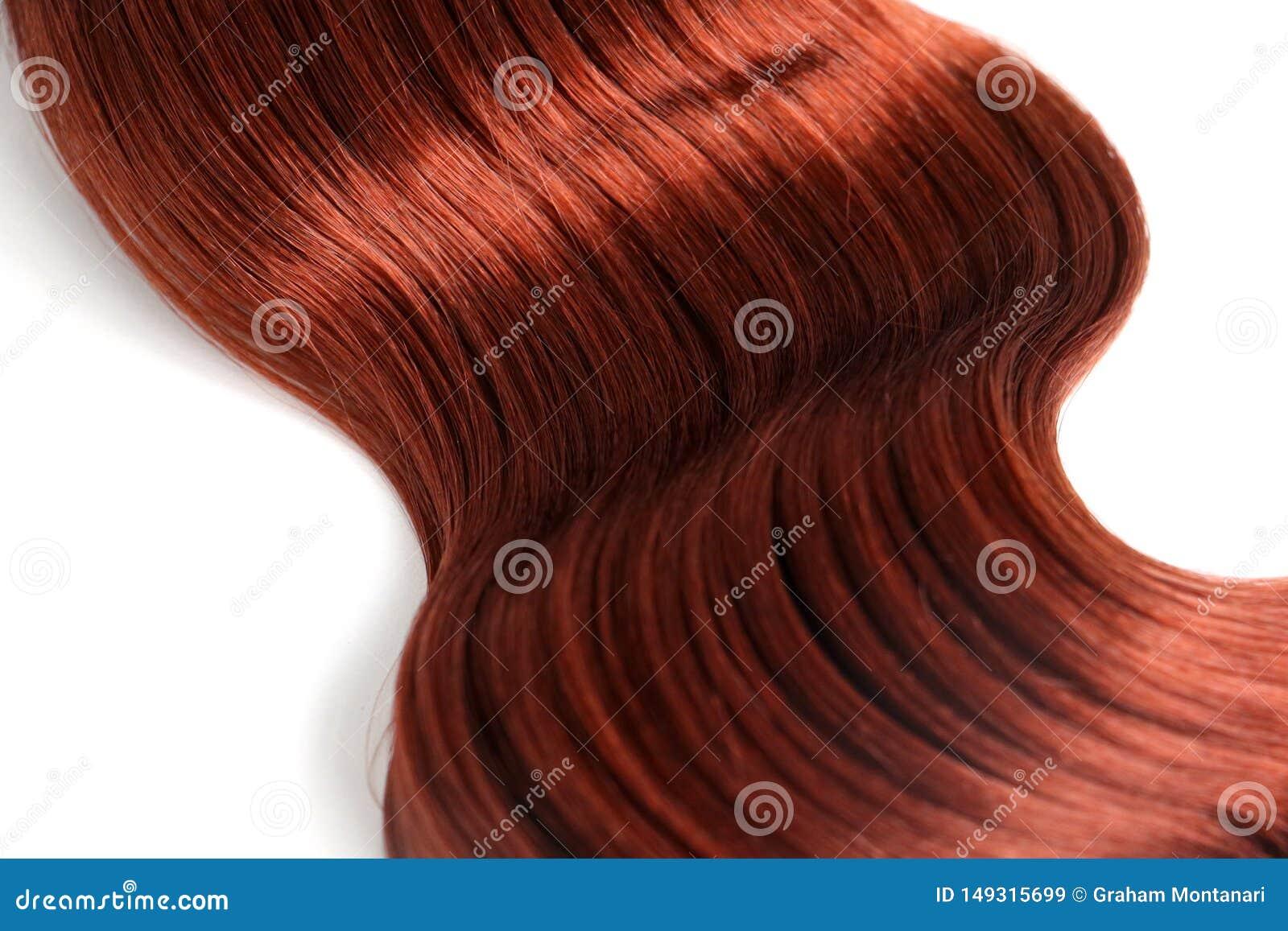 Волнистые красные волосы на белой предпосылке