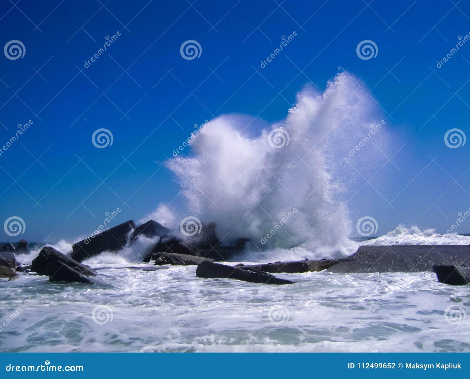 Волны ломая на конкретном волнорезе на ясном голубом небе в a