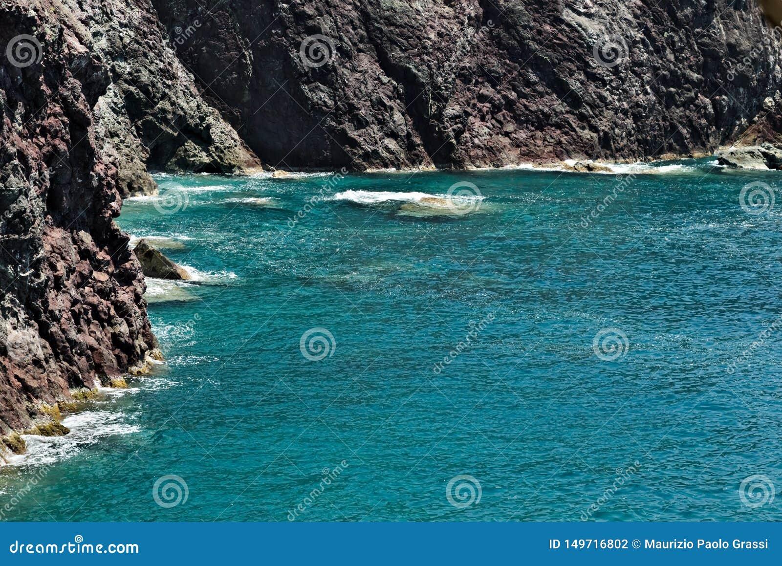 Волны моря ломают на утесах Ligurian горы Около Cinque Terre seascape с голубым морем и темный - красные утесы E