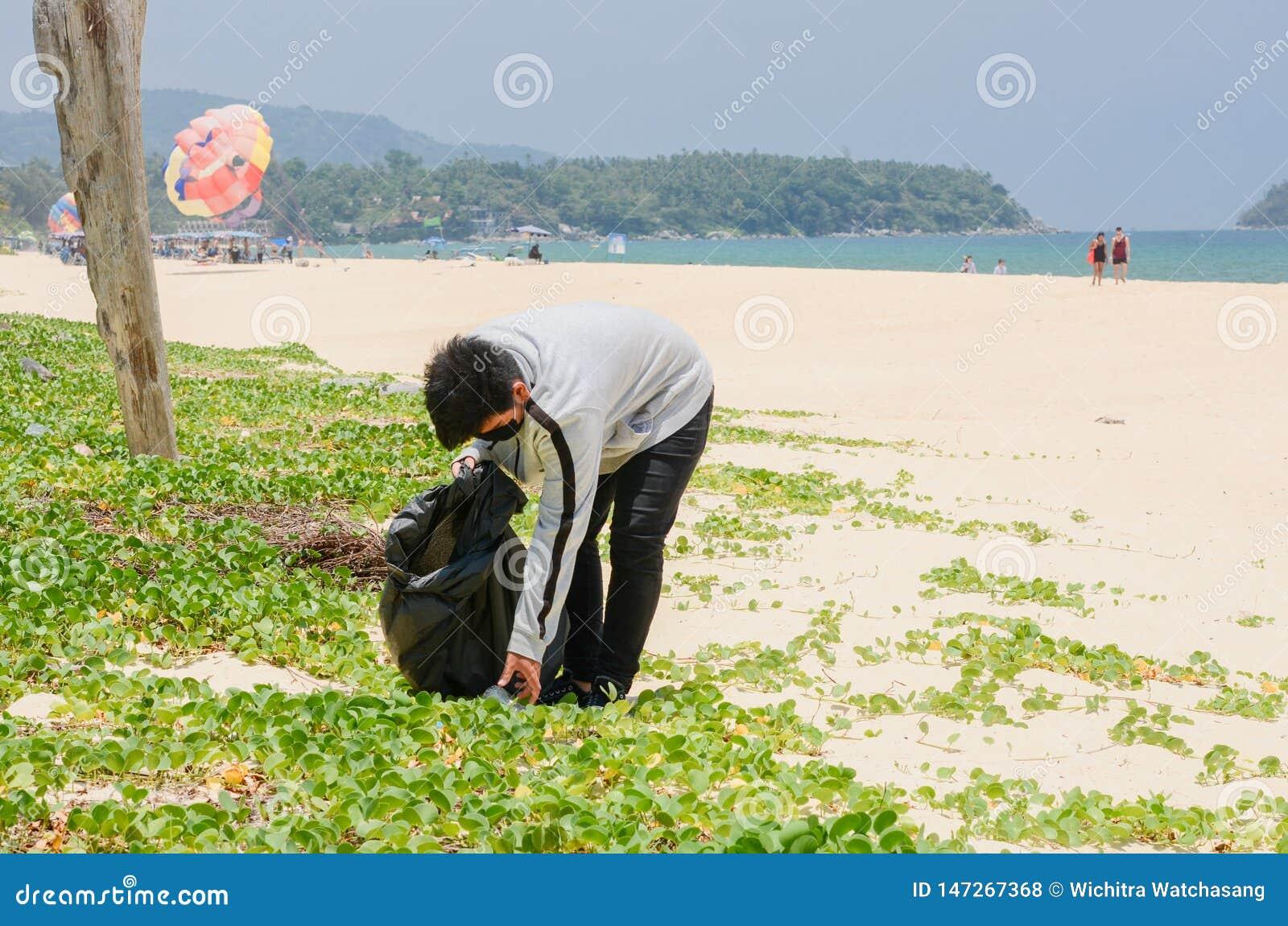 Волонтер ребенка собирая отброс на красивом пляже на пляже Karon