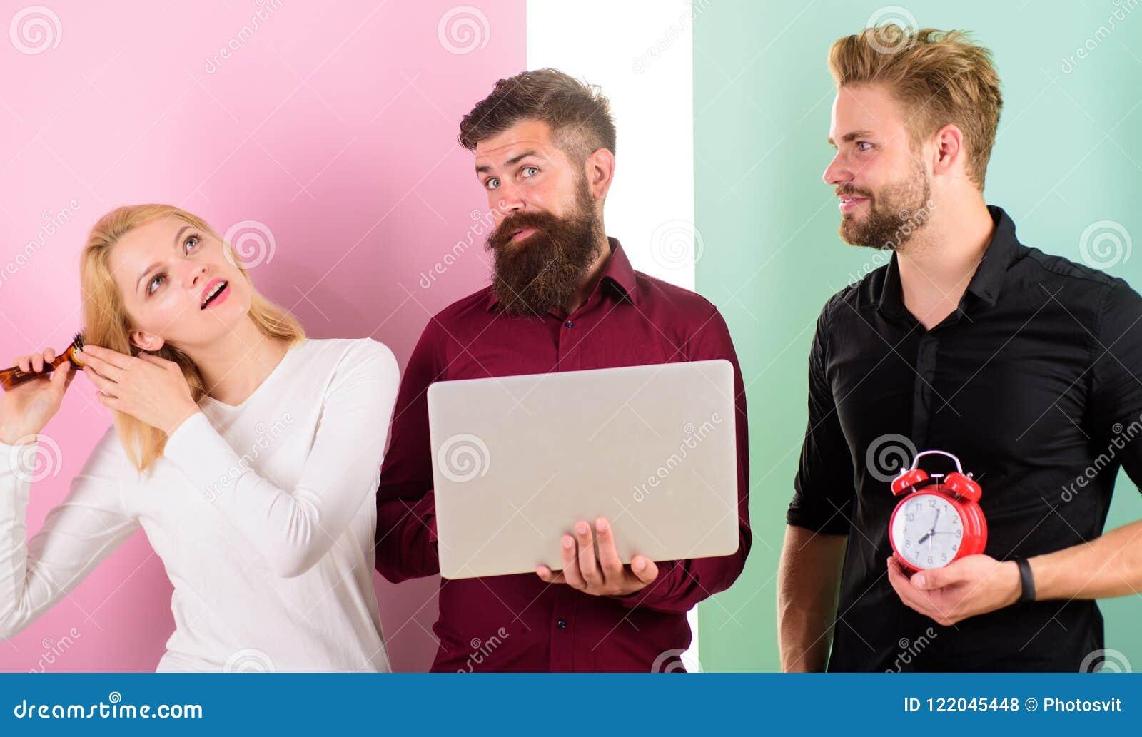 Волосы девушки чистя щеткой пока люди работают с компьтер-книжкой Дисциплина и время Некоторые людей всегда бегут поздно Почему ж