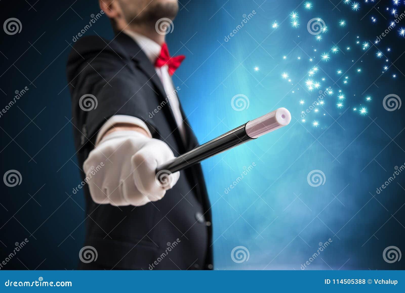 Волшебник или illusionist показывают волшебный фокус Голубой свет этапа в предпосылке