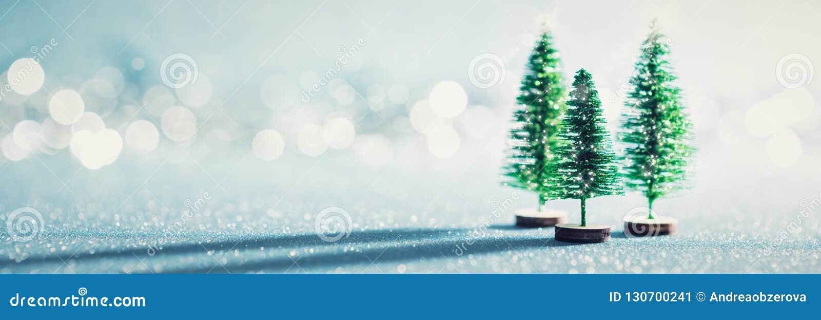 Волшебное миниатюрное знамя страны чудес зимы Вечнозеленые рождественские елки на сияющей голубой предпосылке