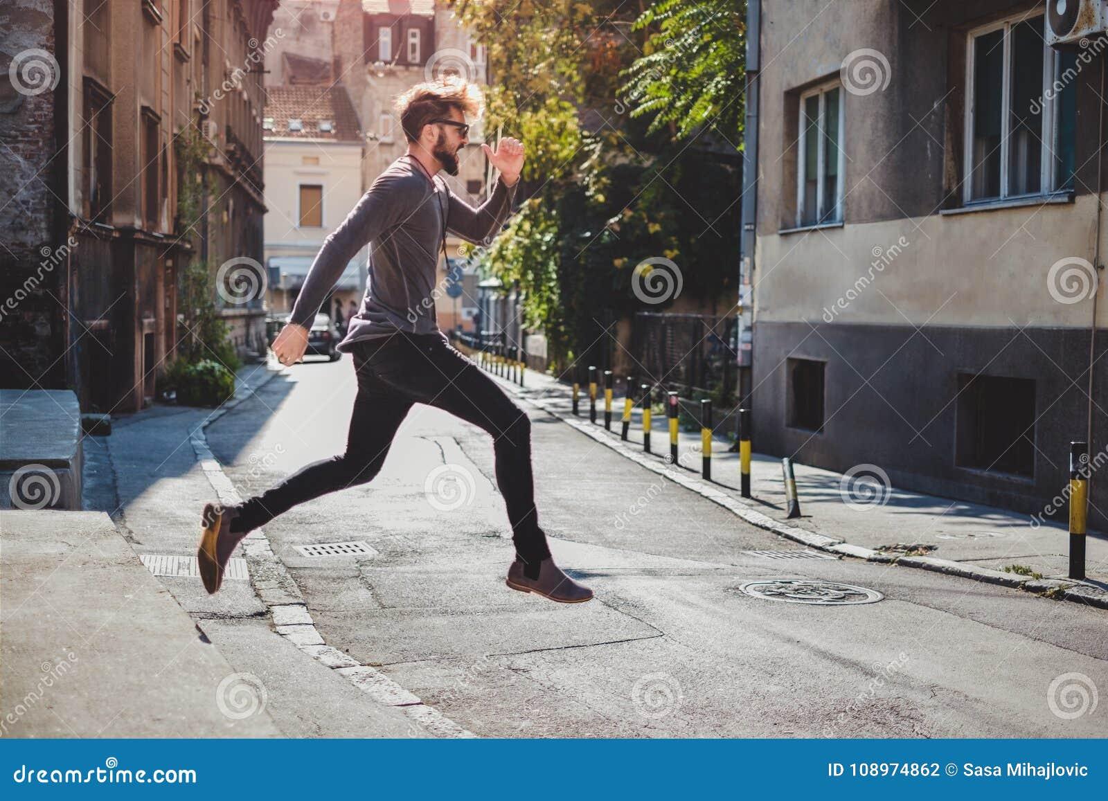 Восторженный битник скачет в улицу с его ртом открытым