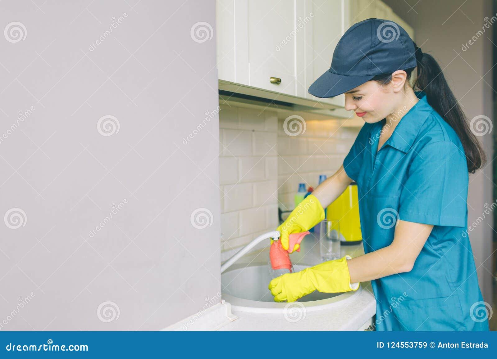 Восхитительная девушка в крышке и форме стоит и работает на раковине Она усмехается немного Девушка профессиональный уборщик