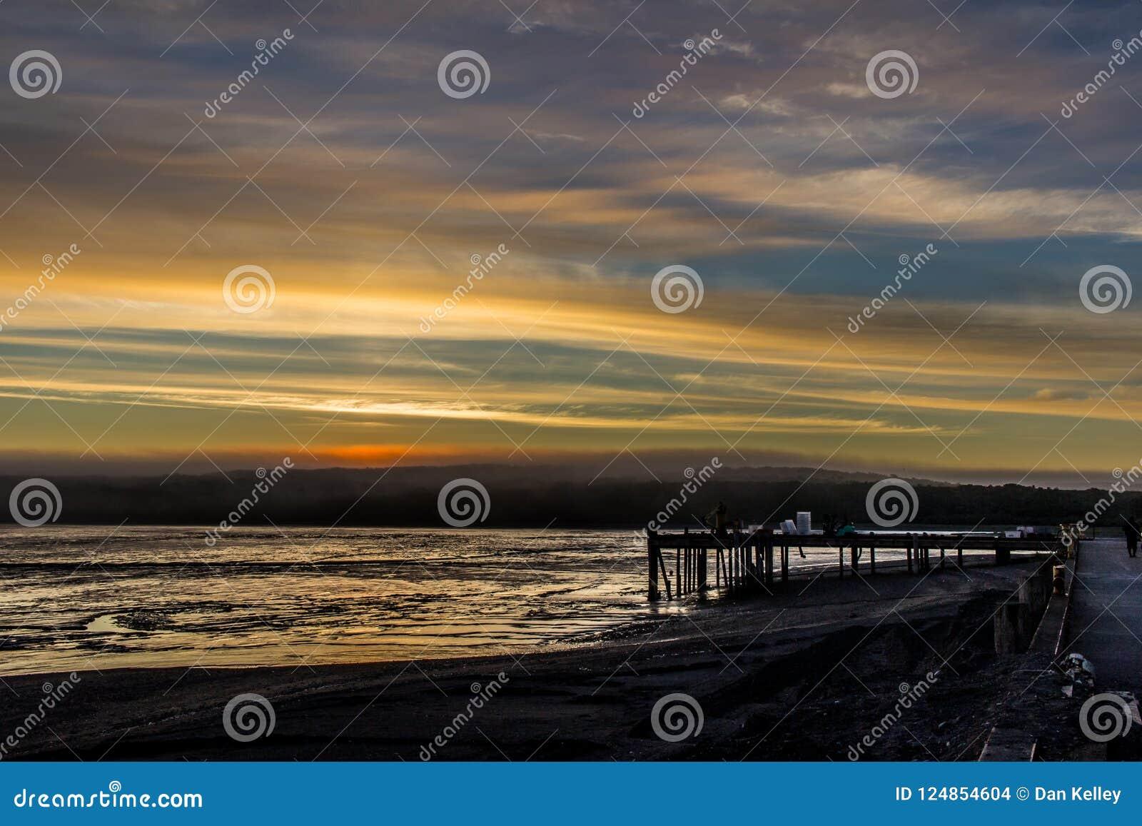 Восход солнца над заливом Бристоля от дока на Ekuk Аляске во время отлива