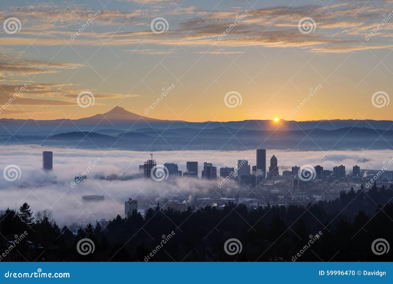 Восход солнца над туманным городским пейзажем Портленда с клобуком Mt