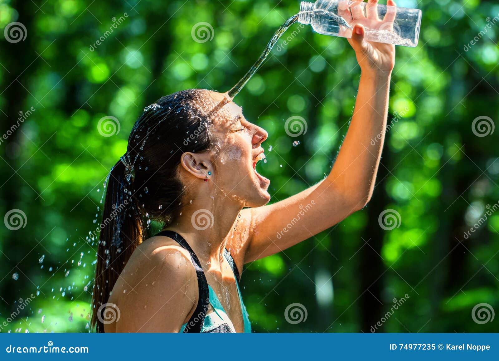 Вода девушки лить на стороне после разминки