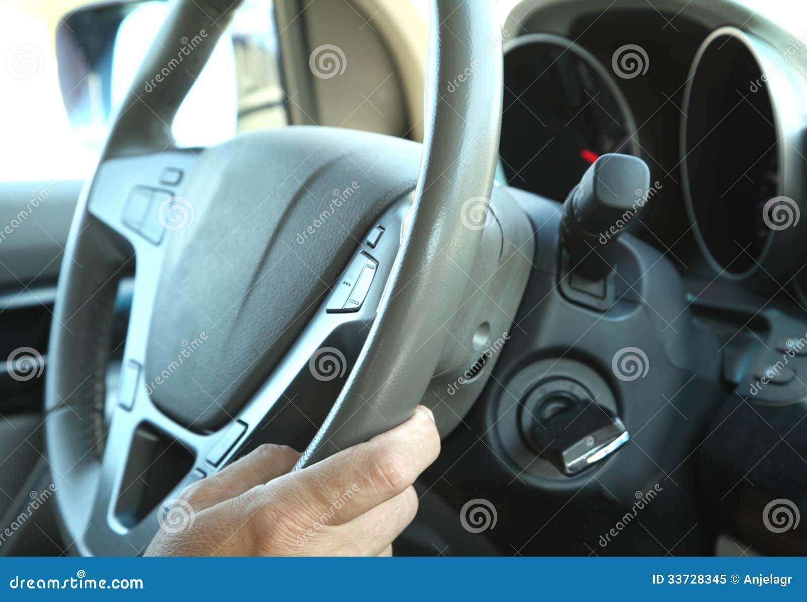 Водитель в автомобиле держа рулевое колесо