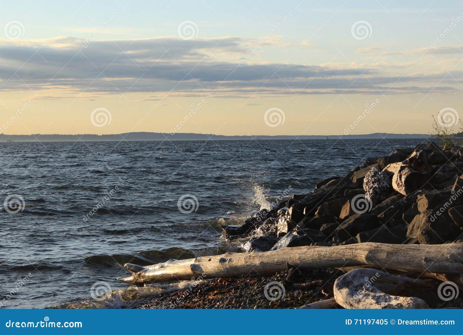 Волна на скалистом береге на заходе солнца