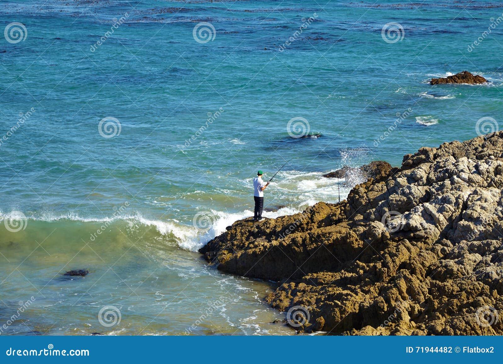 Волны бить против прибрежных утесов на скалах