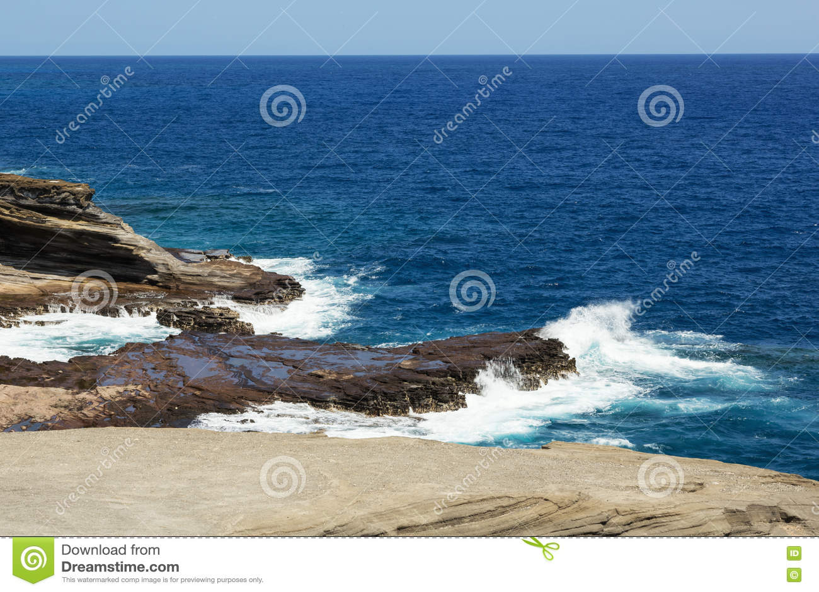 Волны ломая на скалах около бдительности Lanai