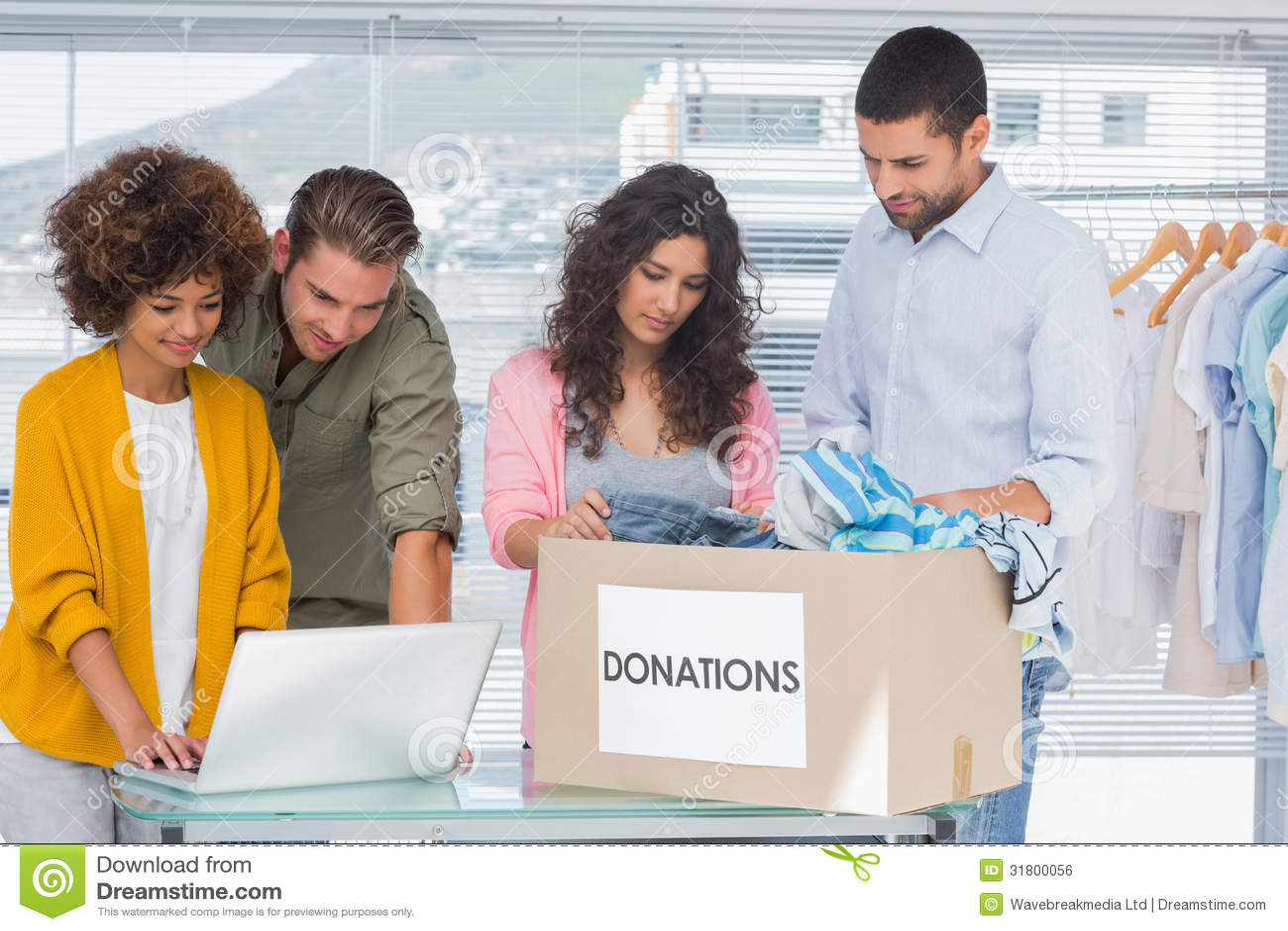Волонтеры используя компьтер-книжку и принимающ одежды от коробки призрения