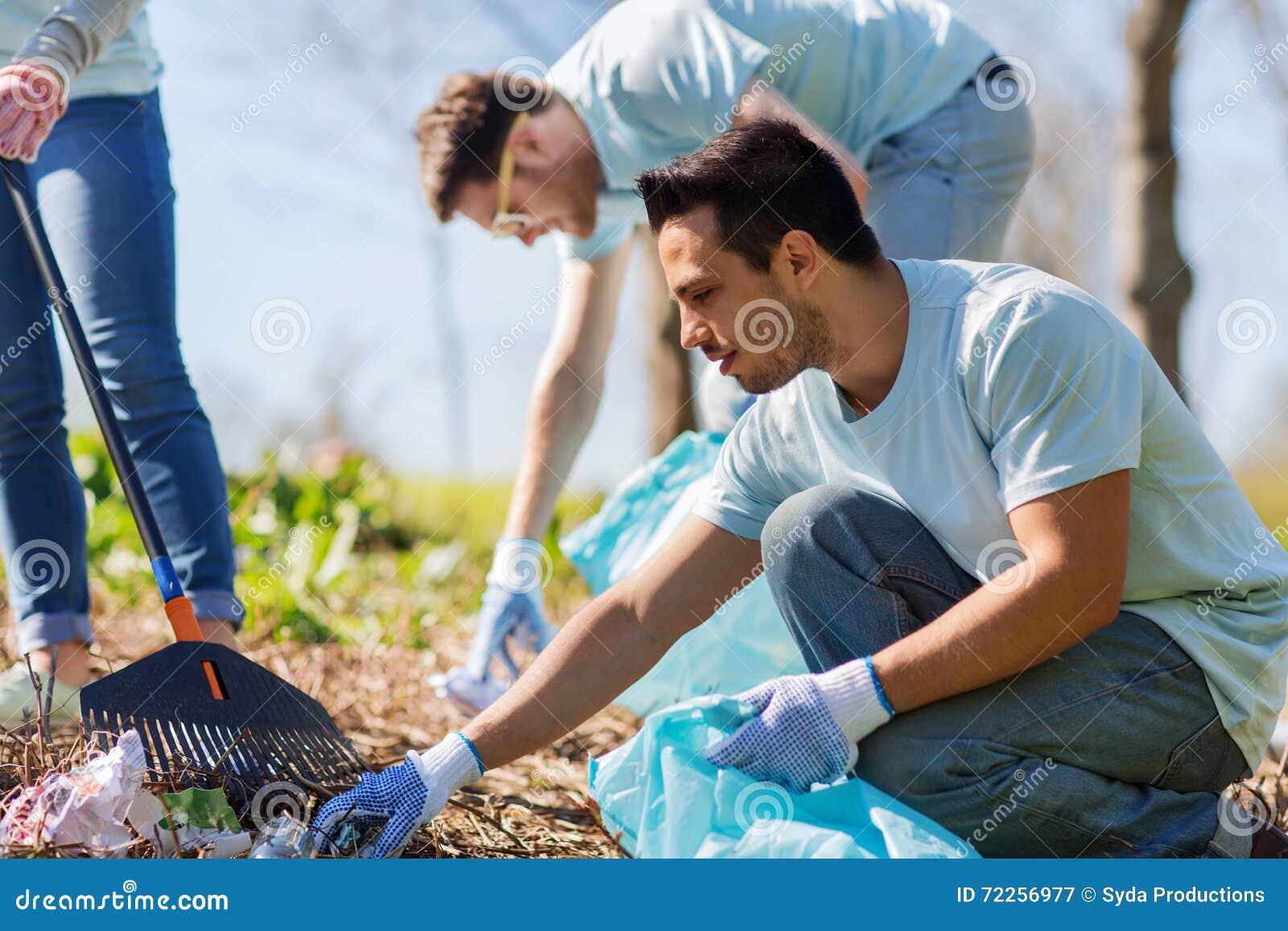 Волонтеры при сумки отброса очищая район парка