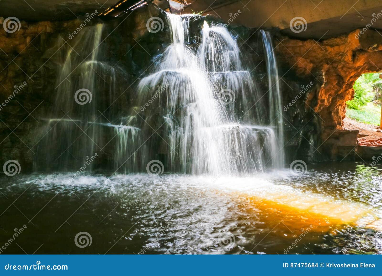 Водопад в парке в солнечном дне