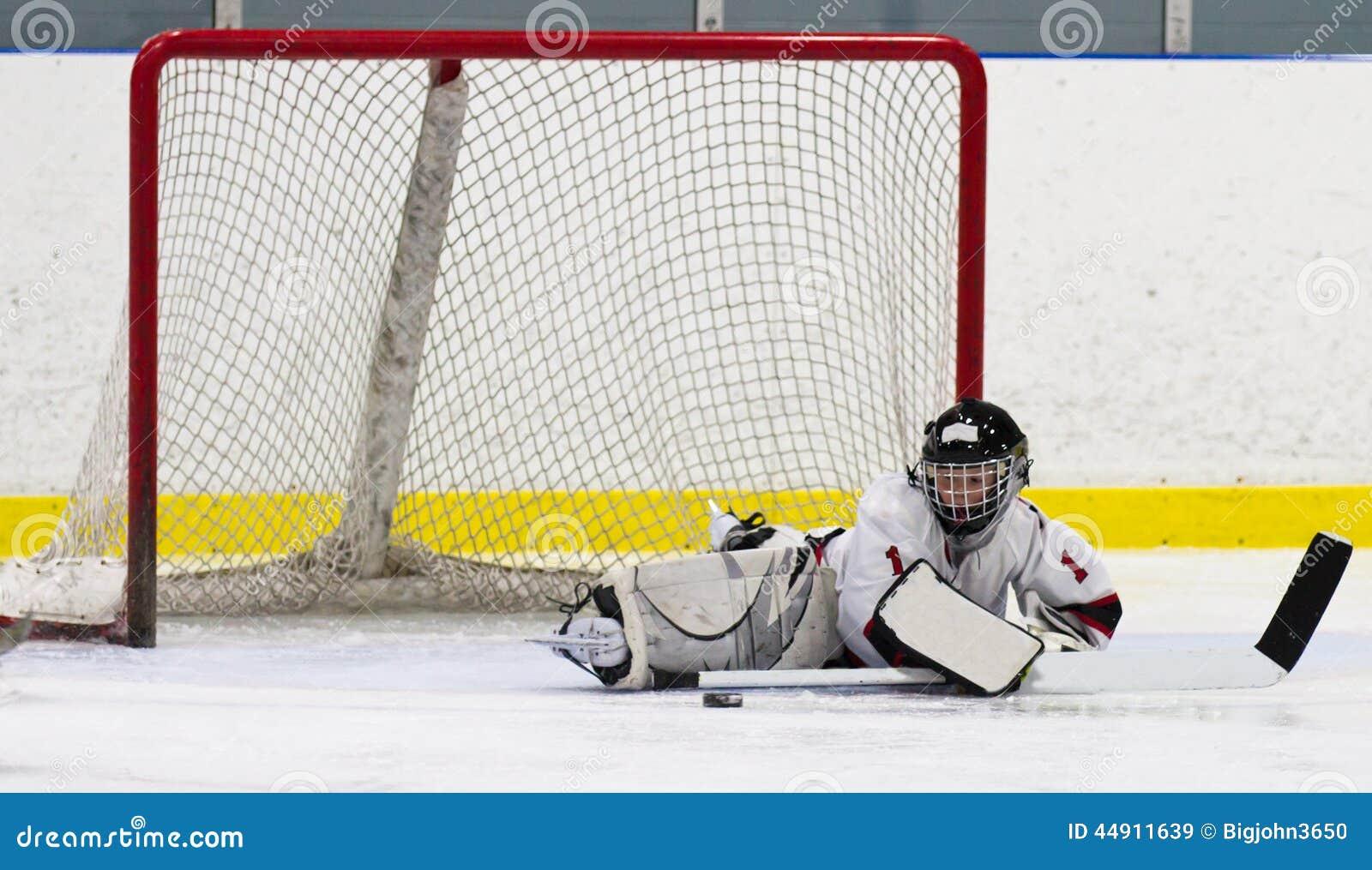 Вратарь хоккея ребенка делая спасение