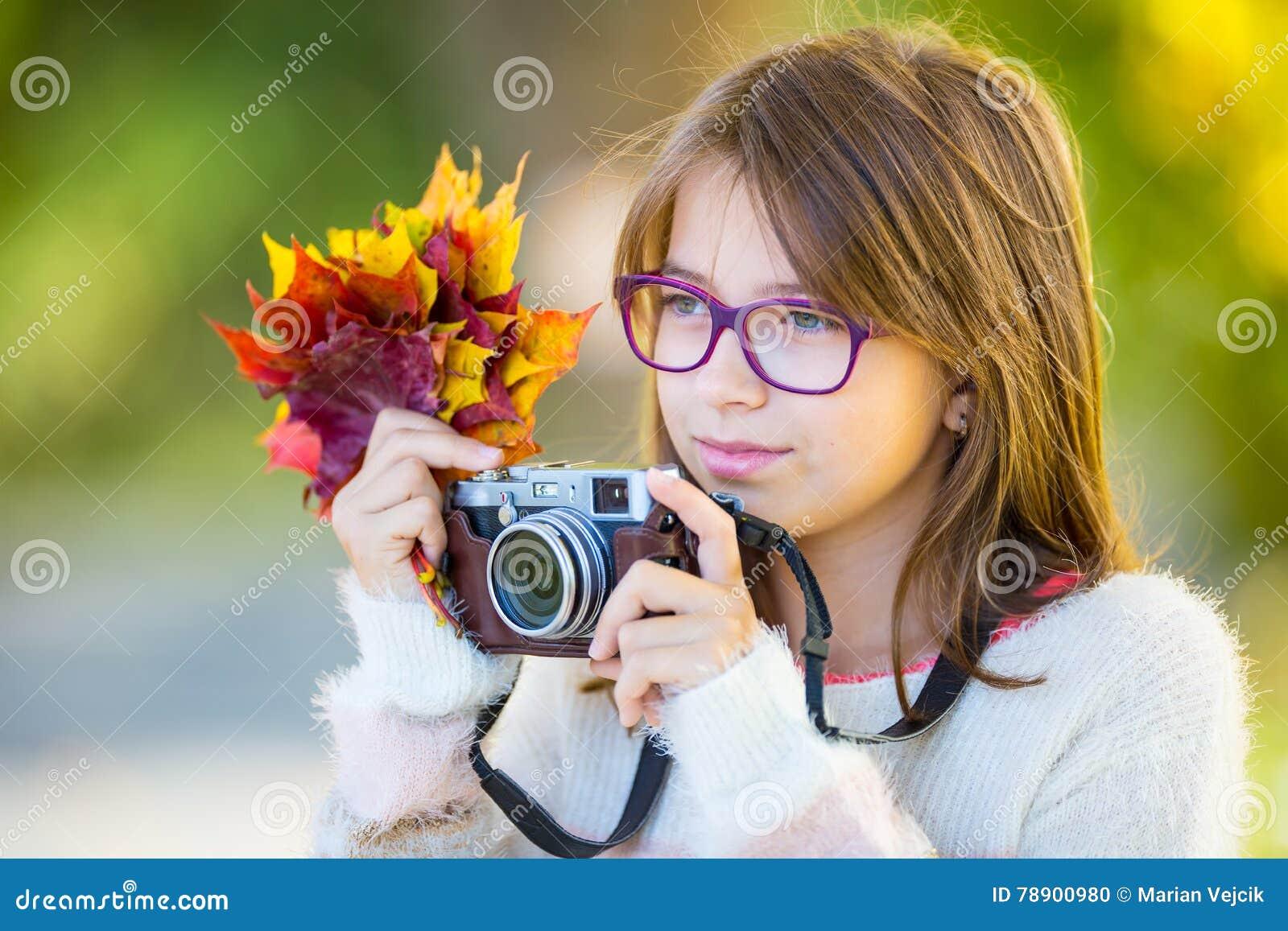 Время осени Подростковая привлекательная милая маленькая девочка с букетом осени и ретро камерой Сезон осени фотографа маленькой