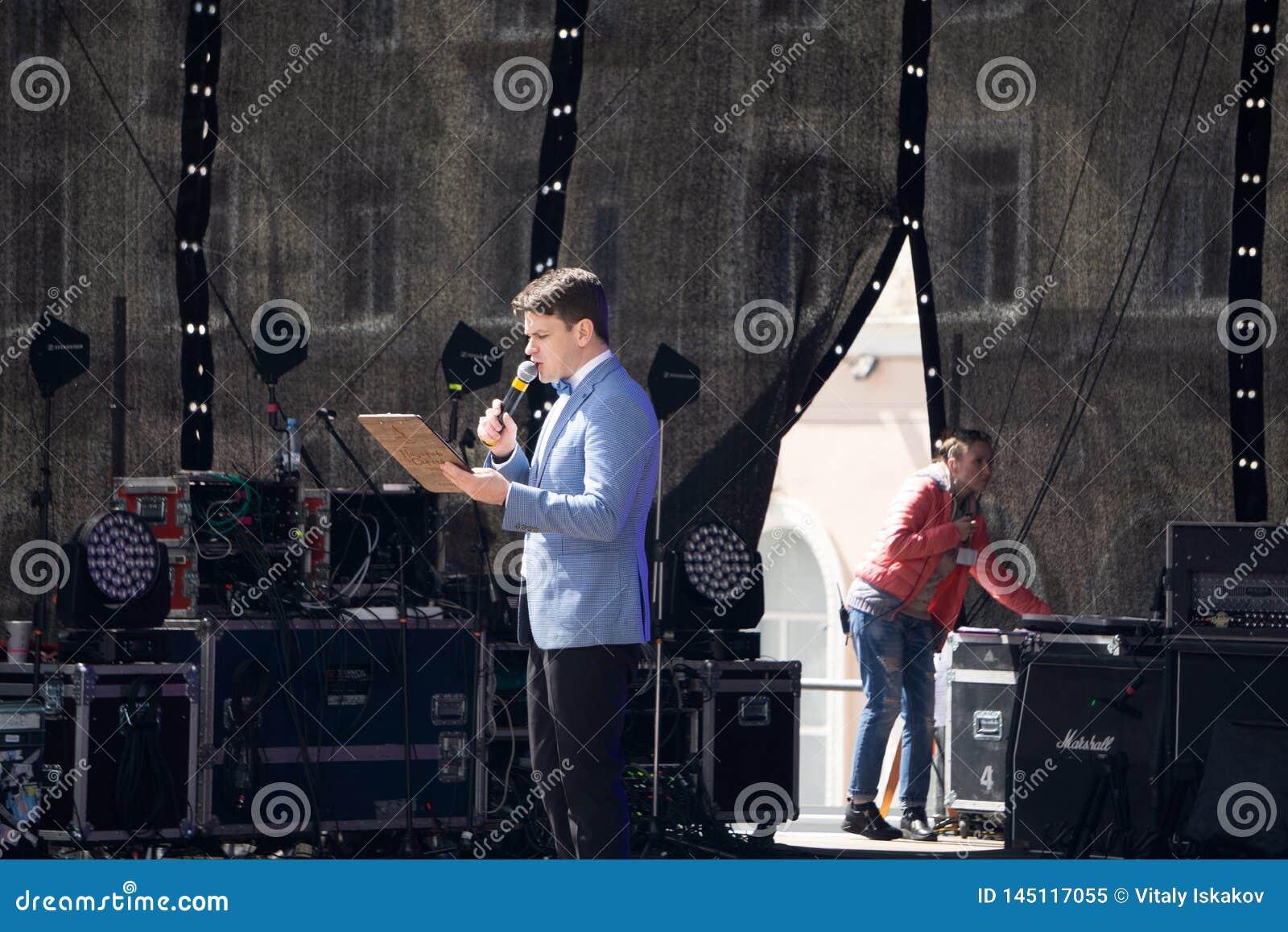 Вручитель с рукой вверх по давать представление пока люди аудитории наблюдают в аудитории конференц-зала Де-сфокусированное Blurr