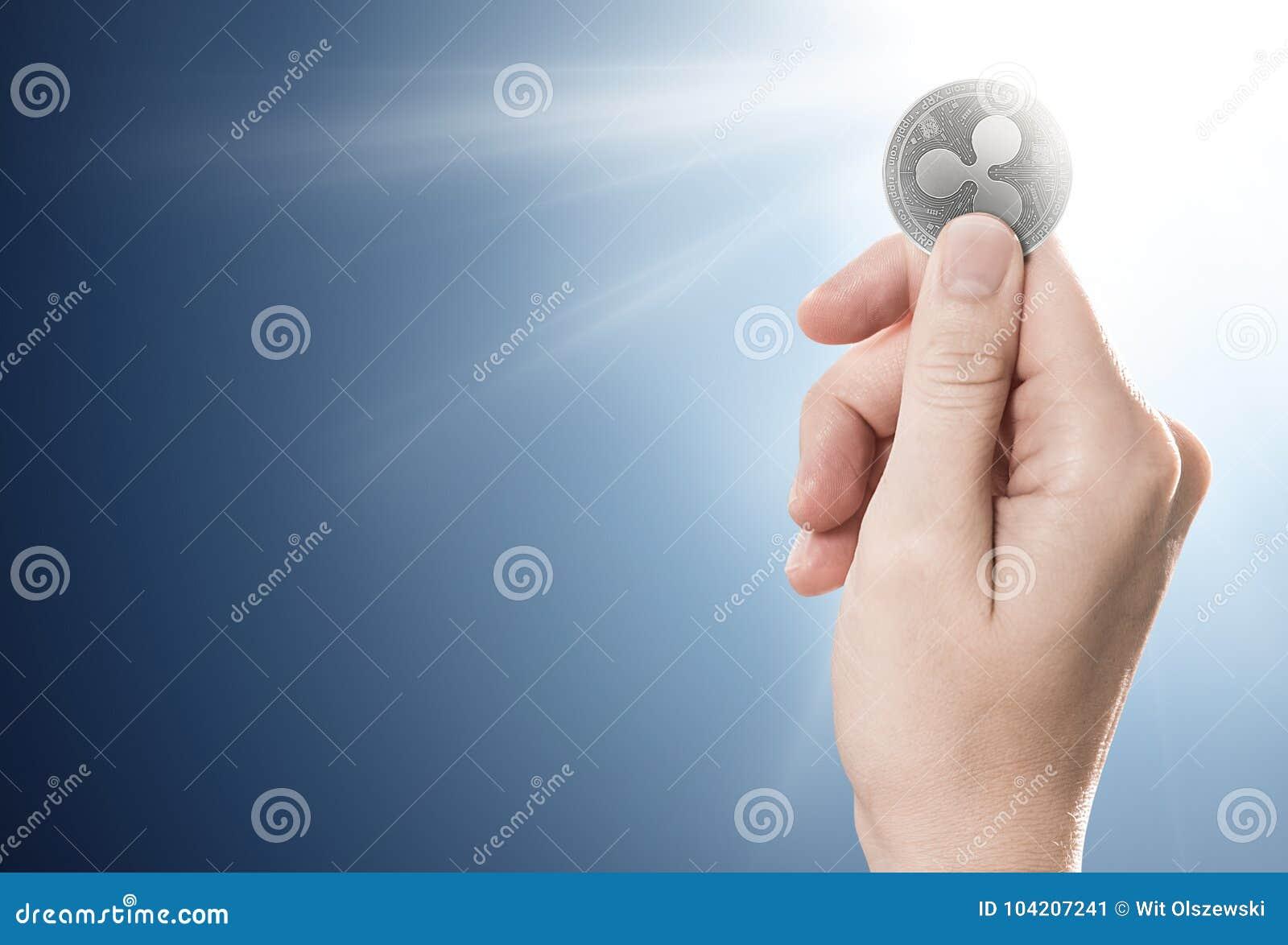 Вручите держать серебряную монетку пульсации на нежно освещенной предпосылке