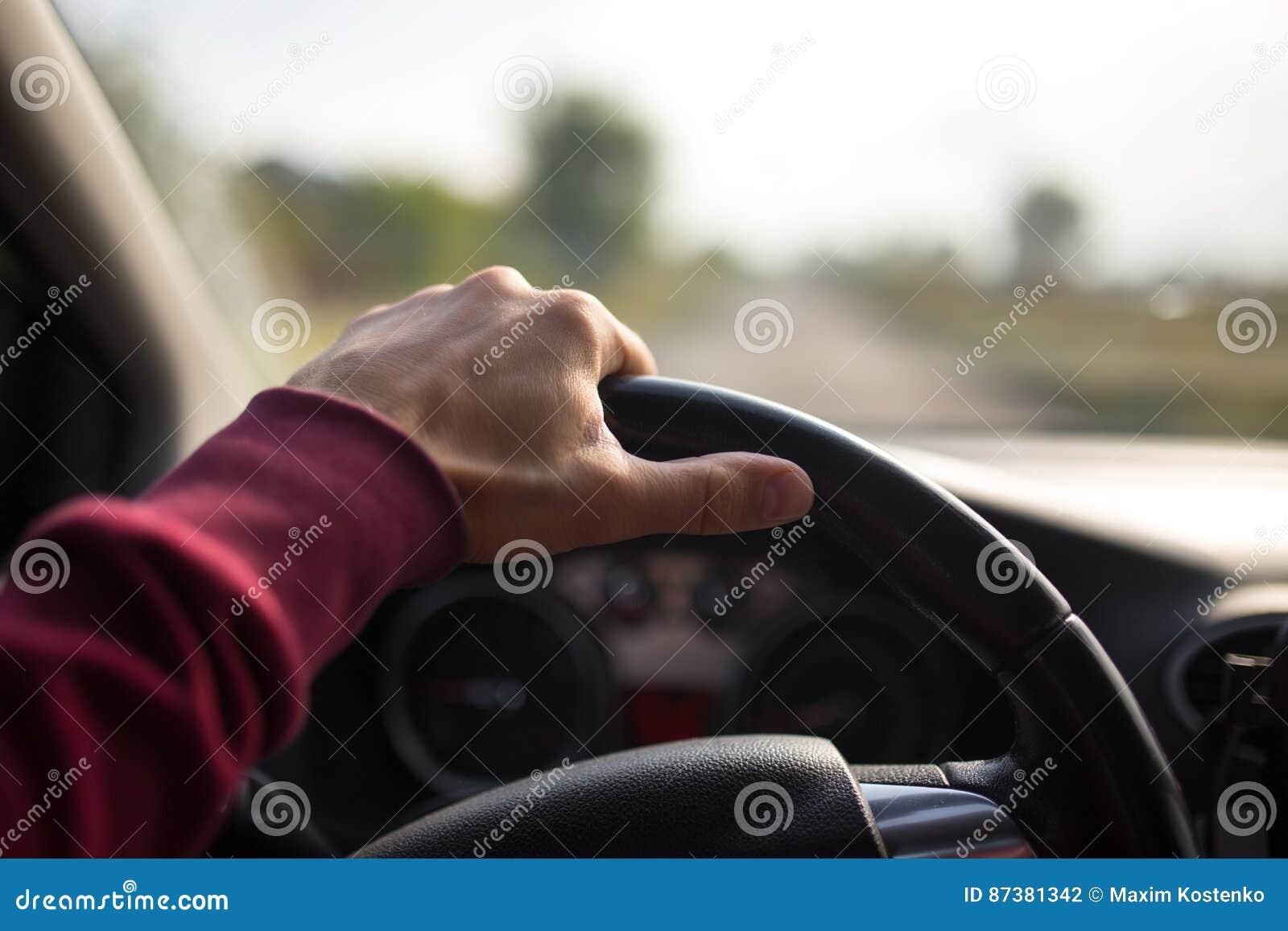 Вручите держать дальше черное рулевое колесо пока управляющ в автомобиле